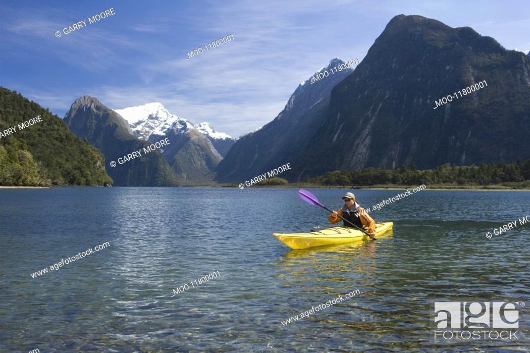 Stock Photo: Man paddling kayak in mountain lake.