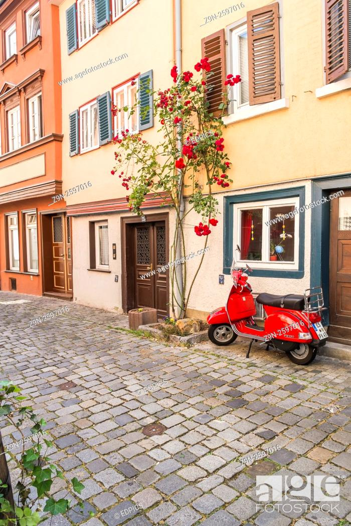 Stock Photo: red vespa scooter in front of historic houses in the historic part of esslingen, baden-wuerttemberg, germany.