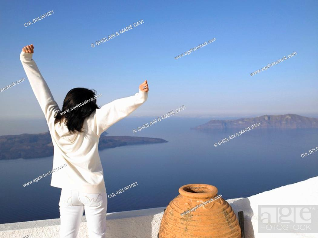 Stock Photo: Woman stretching her arms, sea view.