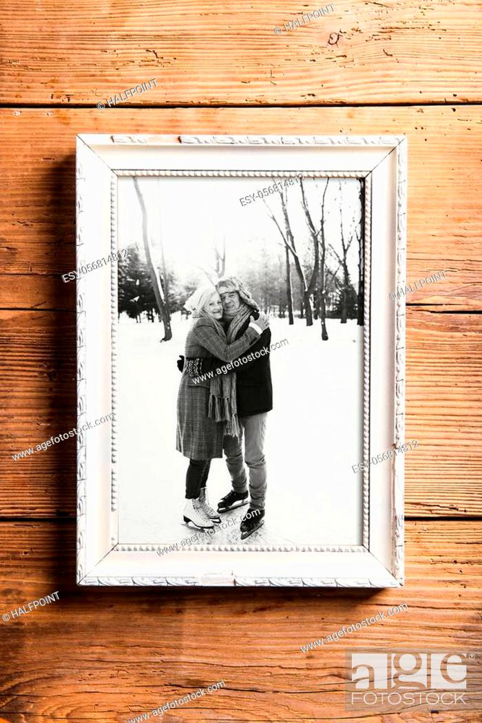 Stock Photo: Black-and-white photo of seniors lying on the ground in white picture frame. Studio shot on brown wooden background.