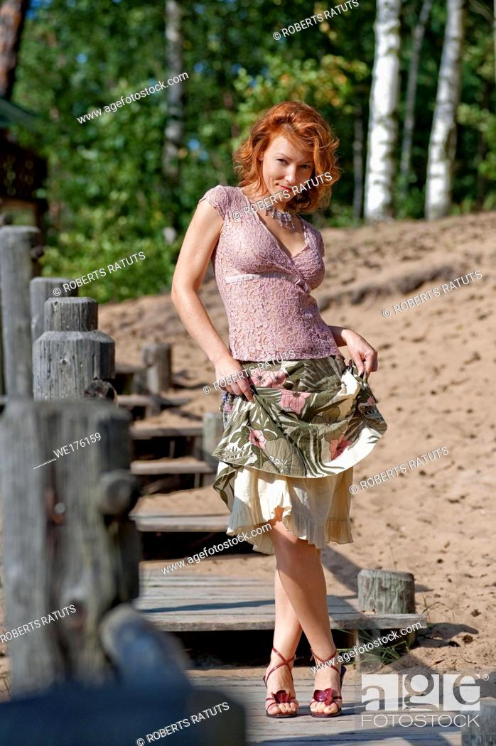 Stock Photo: Red-haired adult woman in dune near the sea.