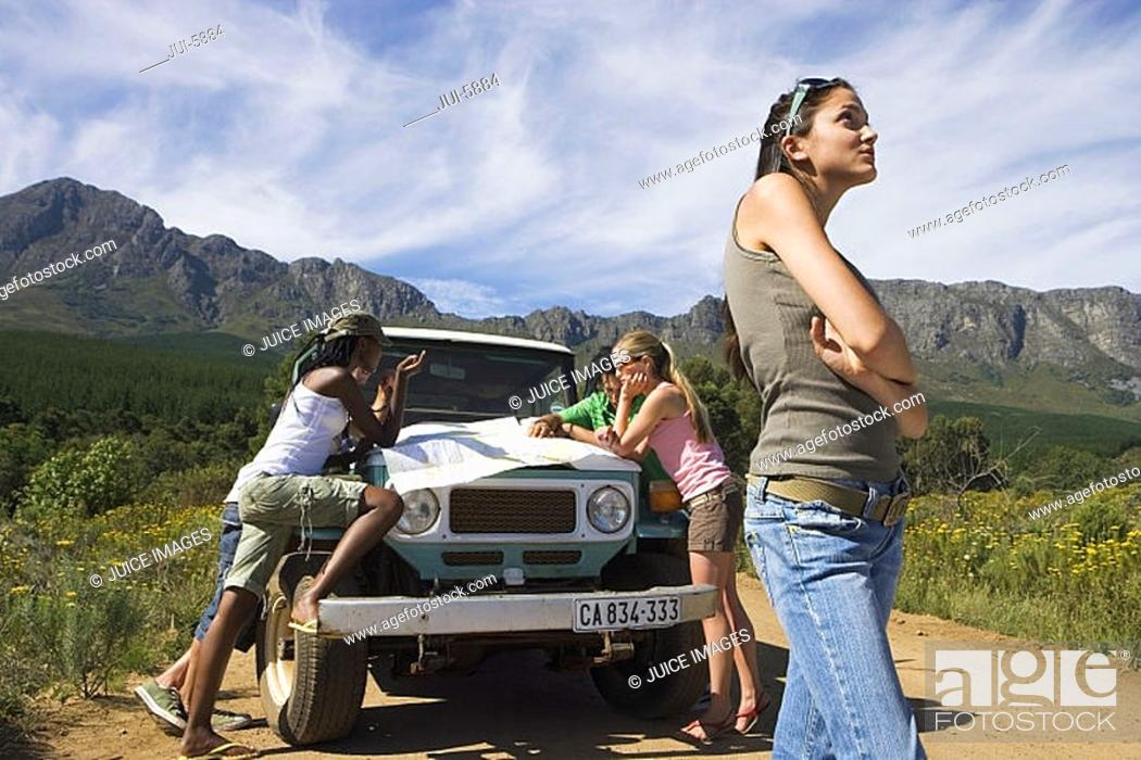 Stock Photo: Four young adults leaning on jeep bonnet on dirt track in mountain valley, consulting map, bored woman waiting impatiently.