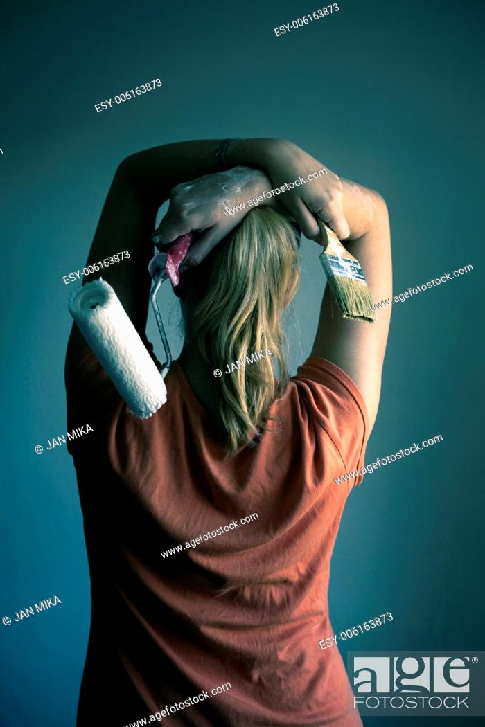 Imagen: Portrait of beautiful blond woman decorating interior with paint roller and paintbrush.