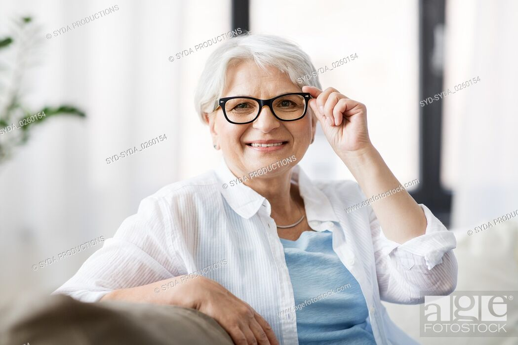 Stock Photo: portrait of happy senior woman in glasses at home.