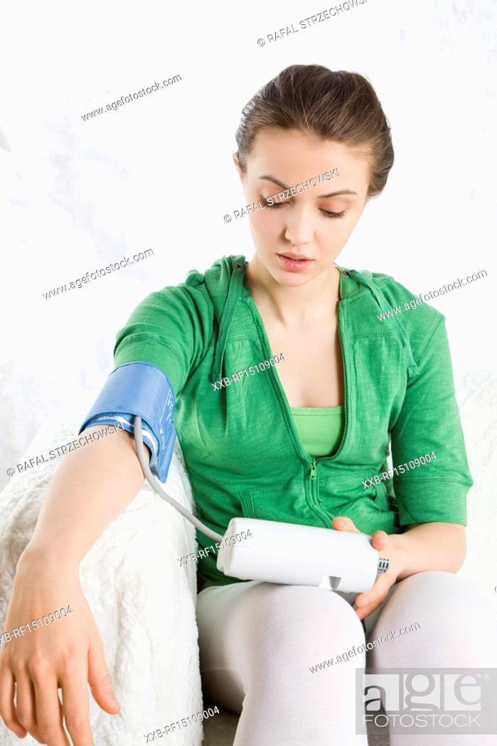 Stock Photo: woman measuring blood preasure.