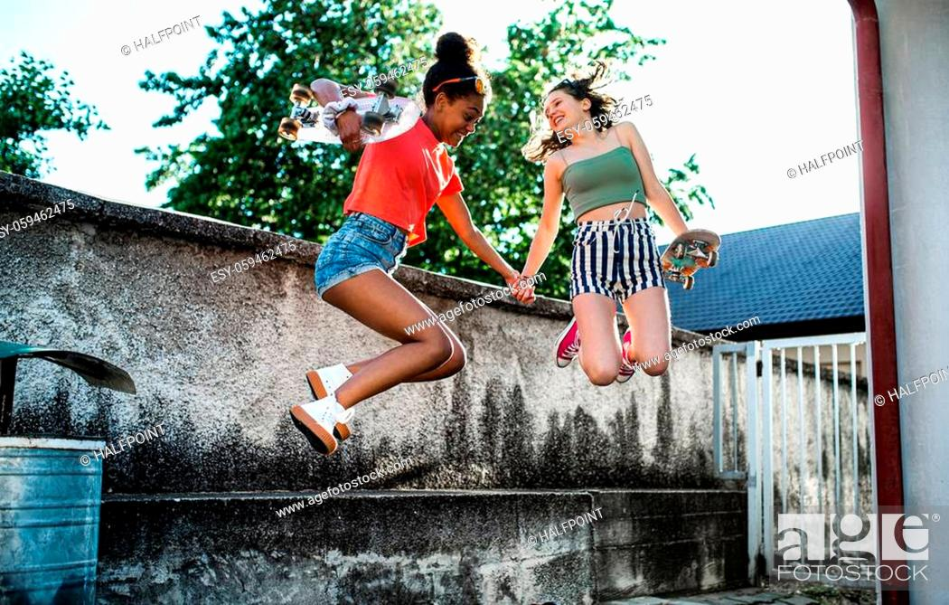 Imagen: Young teenager girls friends with skateboards outdoors in city, jumping by concrete wall.