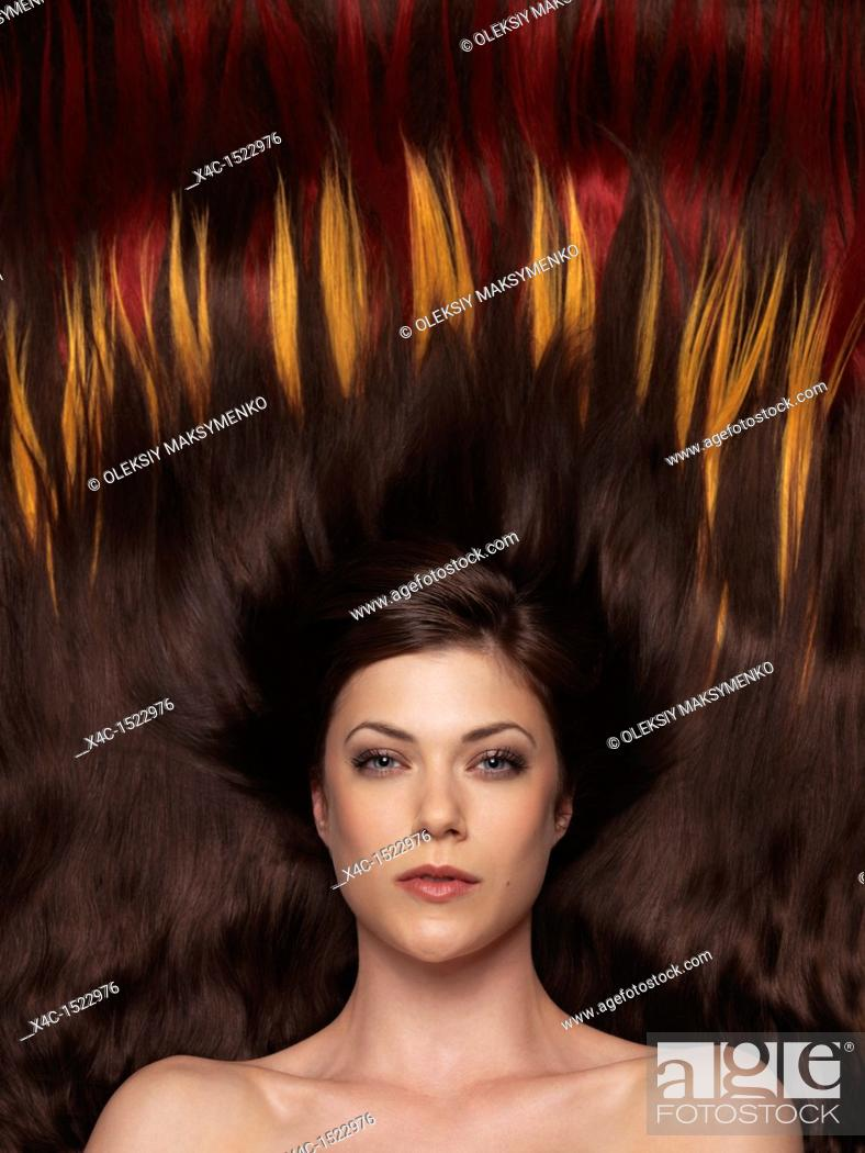 Stock Photo: Beautiful woman with brown hair lying on colorful hair extensions in a shape of fire.