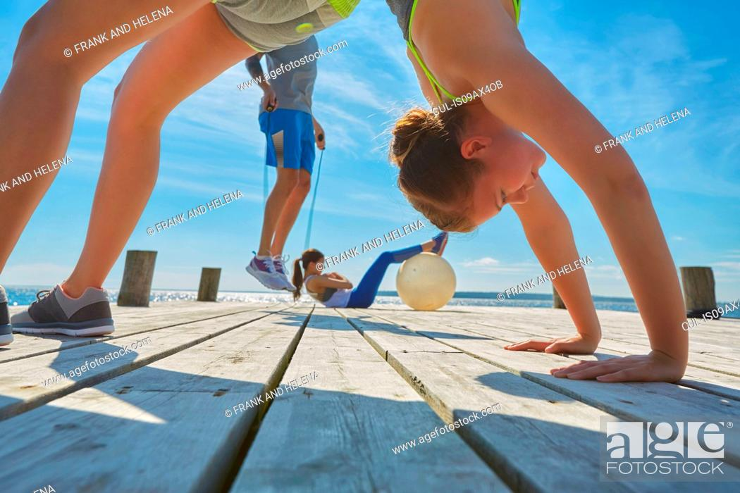 Stock Photo: Friends on pier using exercise equipment.