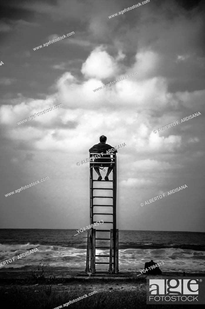 Stock Photo: A man watches the skyline from a lifeguard chair, Caravia, Asturias.