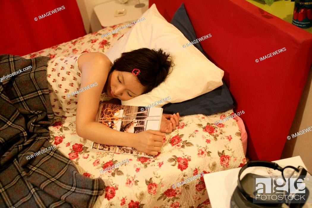 Stock Photo: A young woman sleeps peacefully on the bed after reading a book.