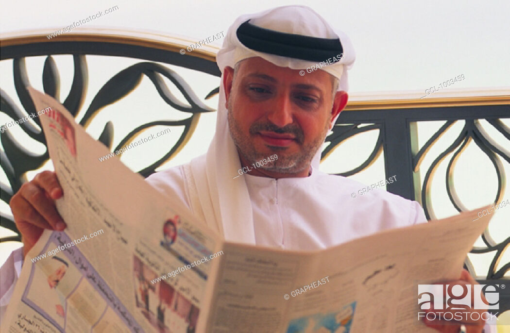 Stock Photo: Businessman reading Arabic newspaper.