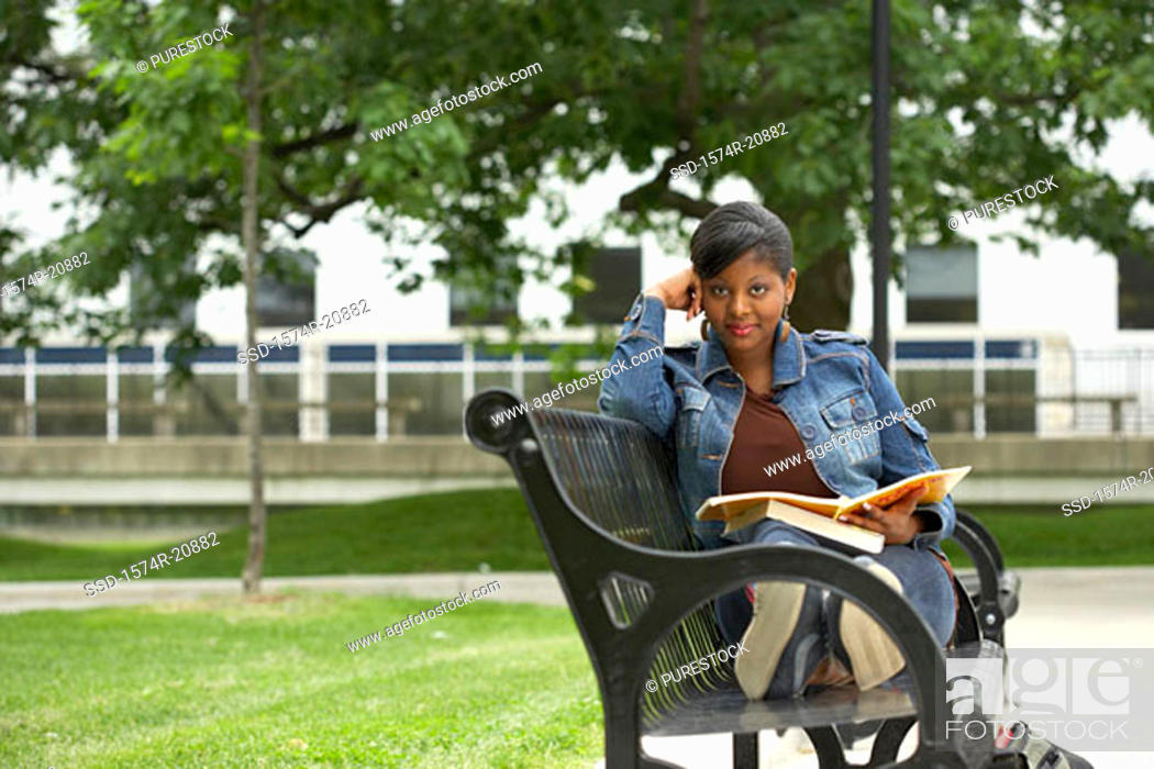 Stock Photo: Portrait of a college student sitting on a bench and holding a book.