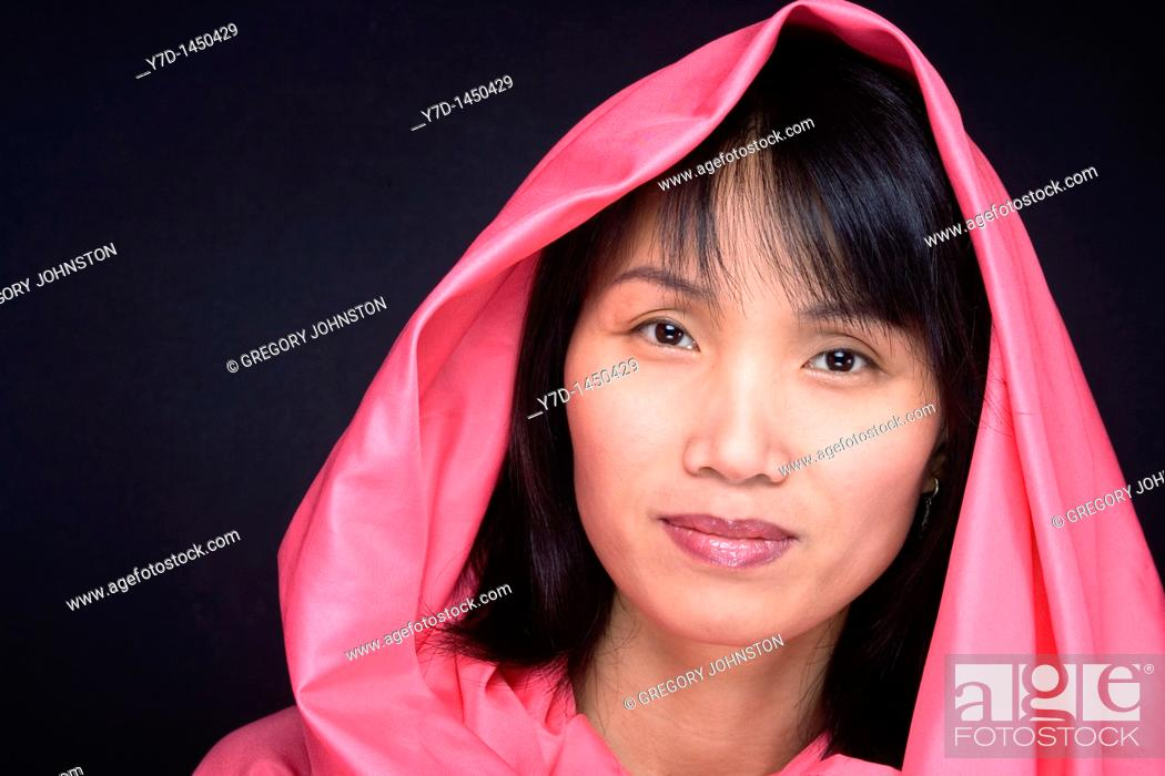 Stock Photo: A portrait of a hooded Asian model against a black background.