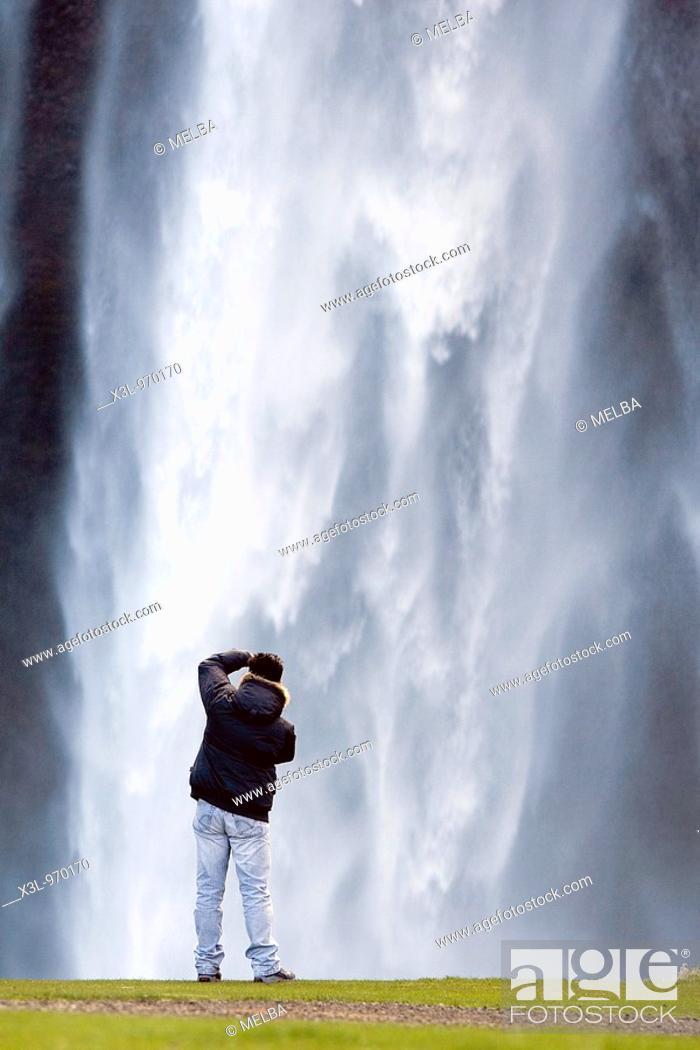 Stock Photo: Photographer in Seljalandsfoss waterfall  Iceland.