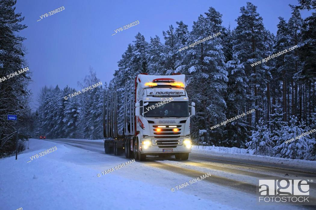 Imagen: Salo, Finland - January 25, 2019: Scania R520 logging truck of E Nousiainen lights up rural highway in the blue hour of winter dusk.