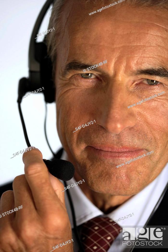 Stock Photo: Senior businessman using a headset.