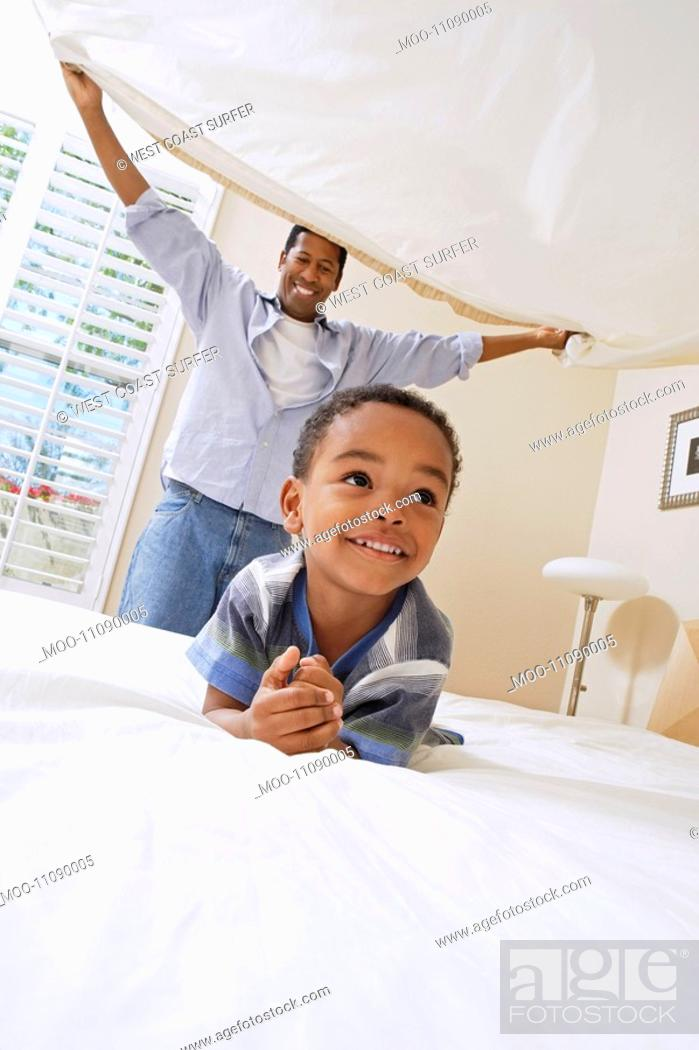 Stock Photo: Father holding bed sheet over son 3-6.