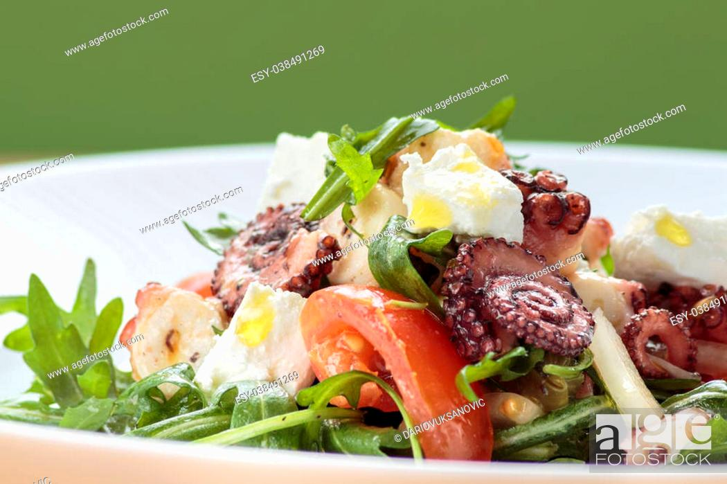 Stock Photo: Octopus salad with rucola, olives and feta cheese on white plate with green background.