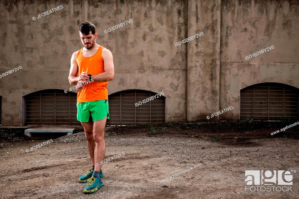 Stock Photo: Young male runner checking smartwatch in front of urban wall.