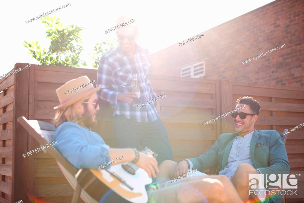 Imagen: Three male friends chatting and playing guitar at rooftop party.