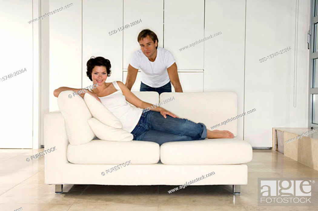Stock Photo: Portrait of a young woman reclining on a couch with a young man standing behind her.