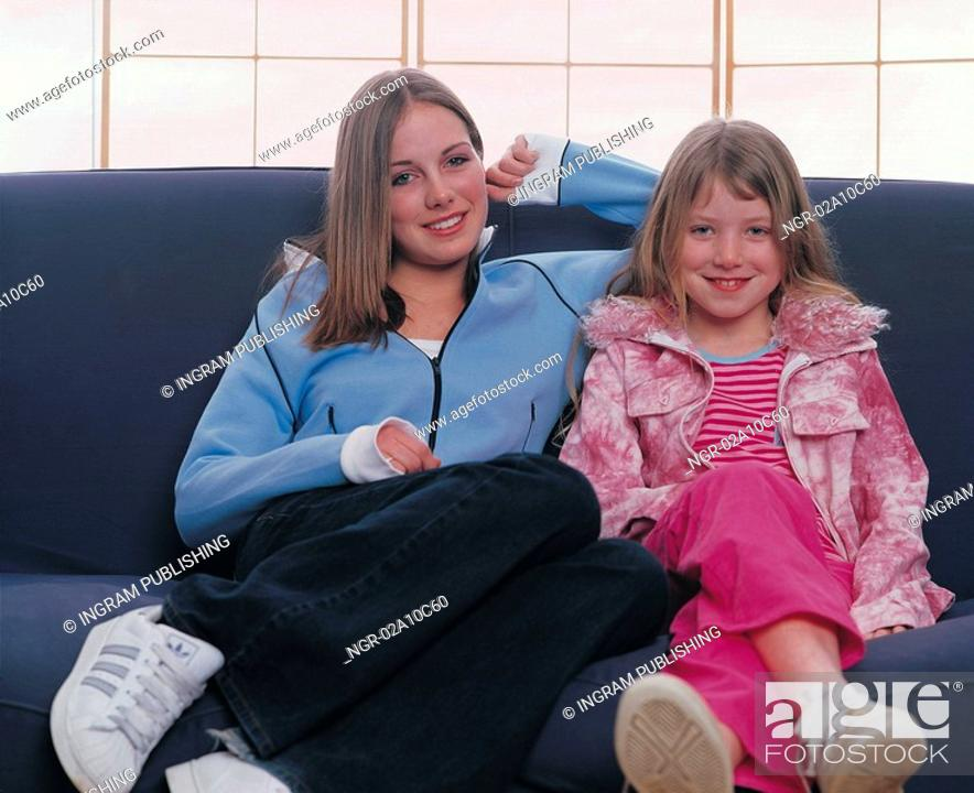 Stock Photo: mother and daughter posing on a couch.
