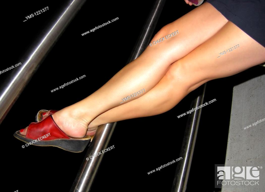 Stock Photo: Woman's Legs Resting on Railing.