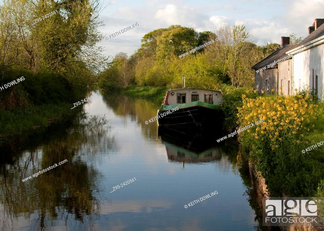 Stock Photo: Original Canal boat moored along a canal sidng near Carlow on the Beautiful river Barrow. Summers evening light lifts the waterline.