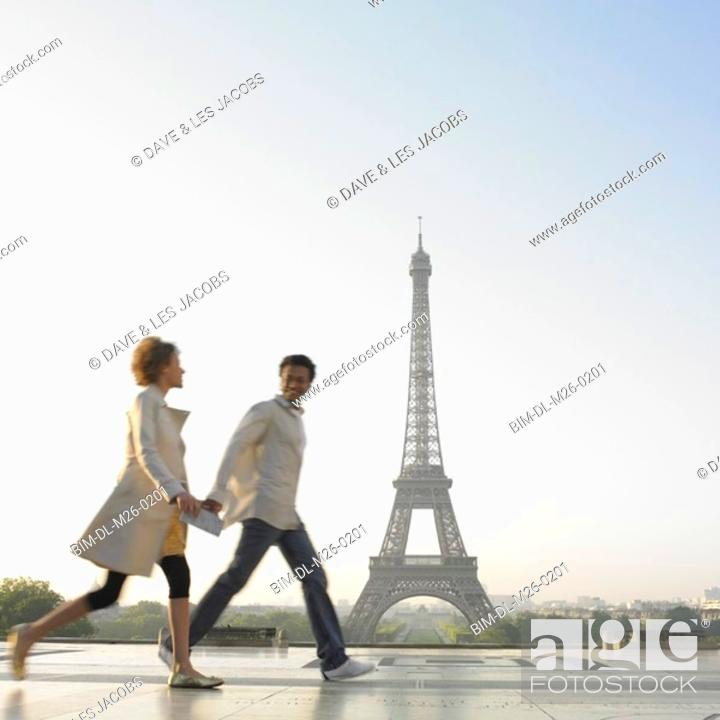 Stock Photo: Couple walking with Eiffel Tower in background.
