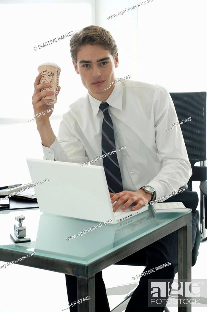 Stock Photo: Business man working with laptop is holding a paper coffee cup.