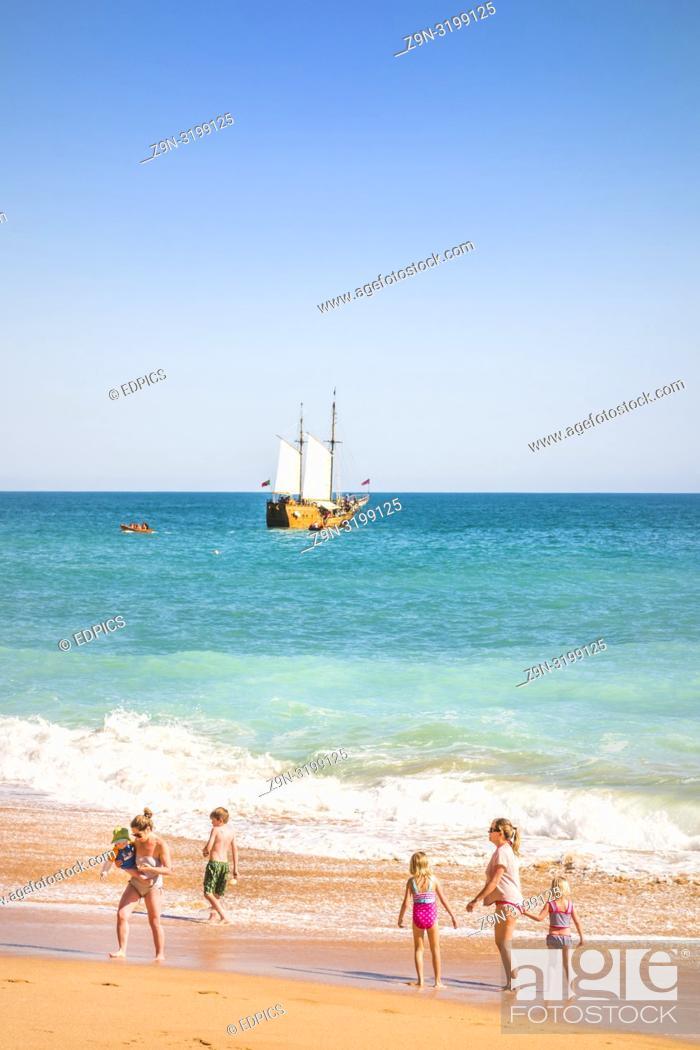 Stock Photo: families at benagil beach with coast tour masted vessel in background, benagil, algarve, portugal.