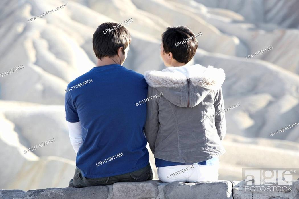 Stock Photo: Couple sitting on stone wall in desert rear view.