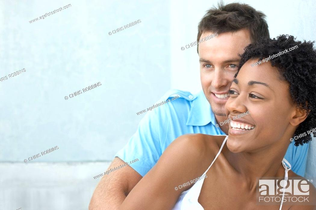 Stock Photo: Smiled couple standing together against wall portrait.
