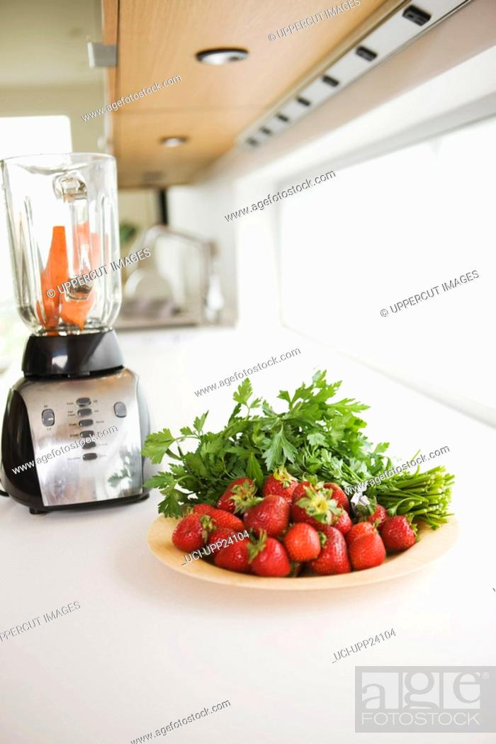 Stock Photo: Close up of strawberries, carrots, and parsley near blender.