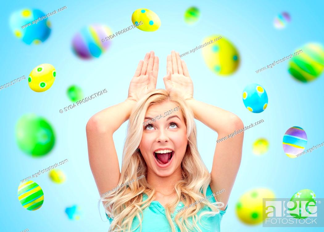 Stock Photo: happy woman making bunny ears over easter eggs.