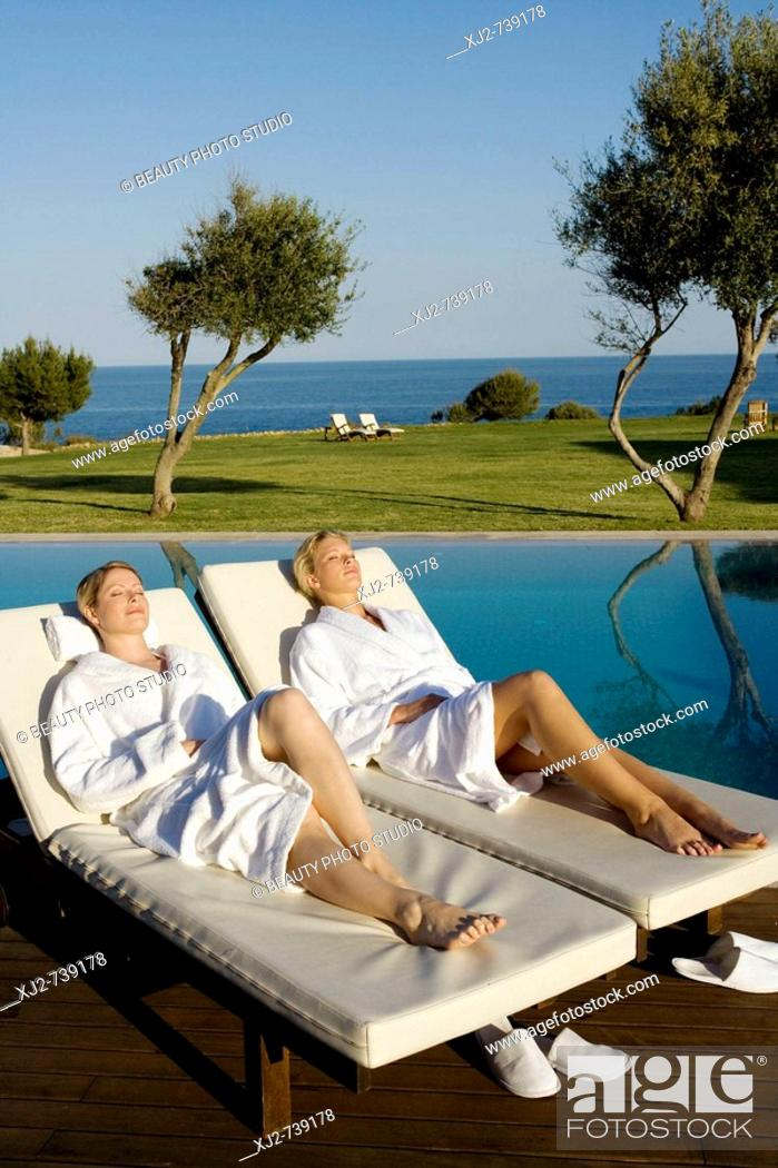 Stock Photo: Two women relaxing on a sun lounger in a Hotel by the sea.