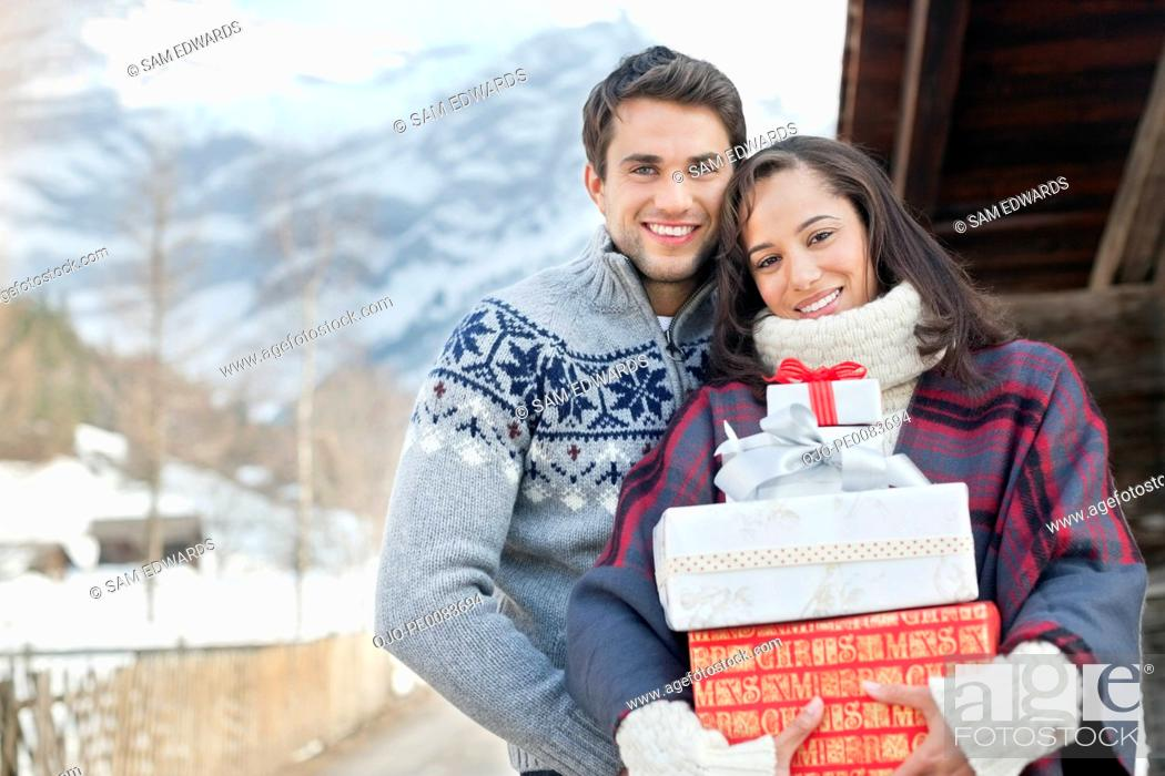 Stock Photo: Portrait of smiling couple holding Christmas gifts.