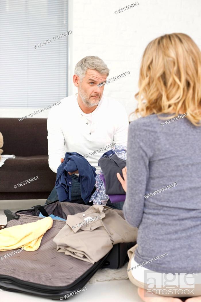 Stock Photo: Germany, Leipzig, Couple packing suitcase.