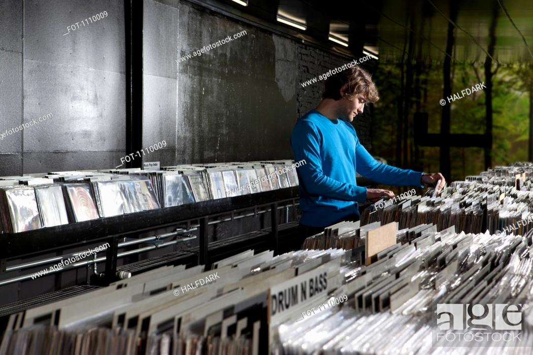 Stock Photo: A young man searching through records in a record store.