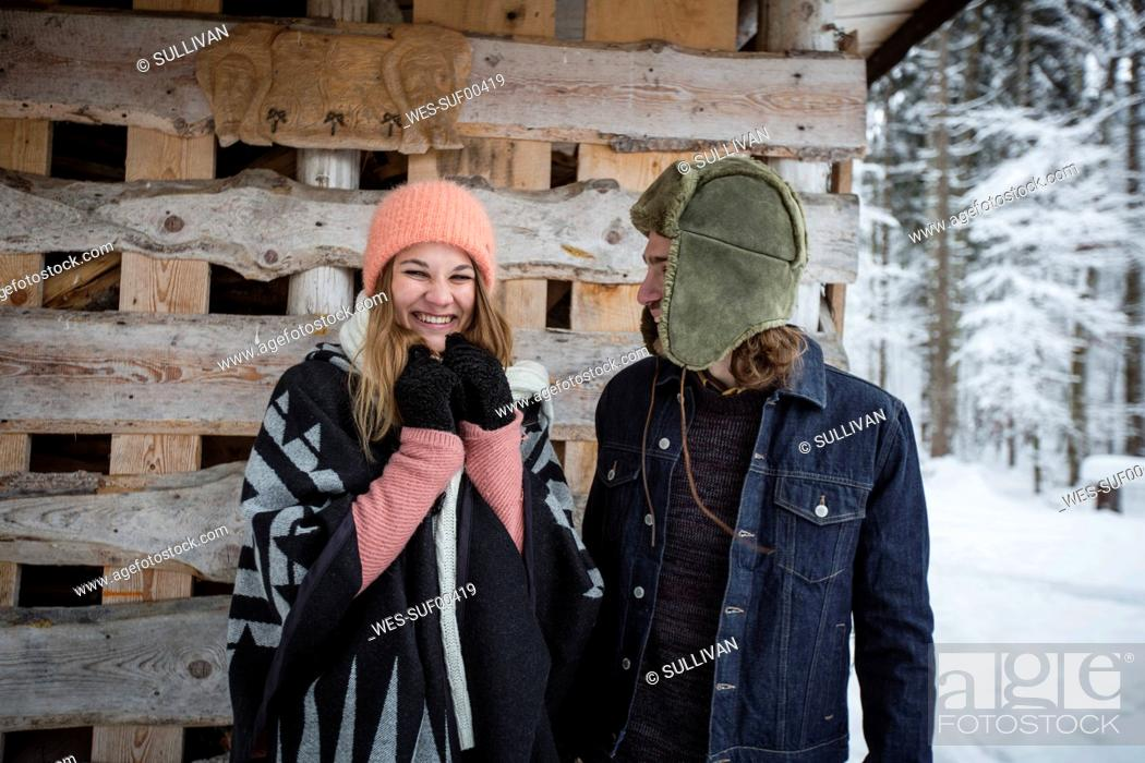 Stock Photo: Portrait of happy couple in front of wood pile outdoors in winter.