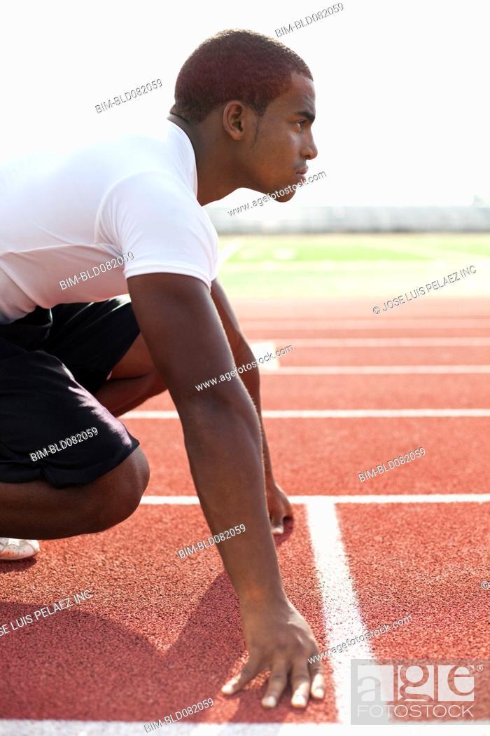 Stock Photo: Black athlete crouching at track starting line.