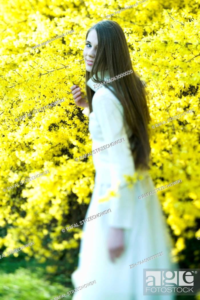 Stock Photo: Teenage girl standing next to flowering tree, smiling over shoulder at camera.
