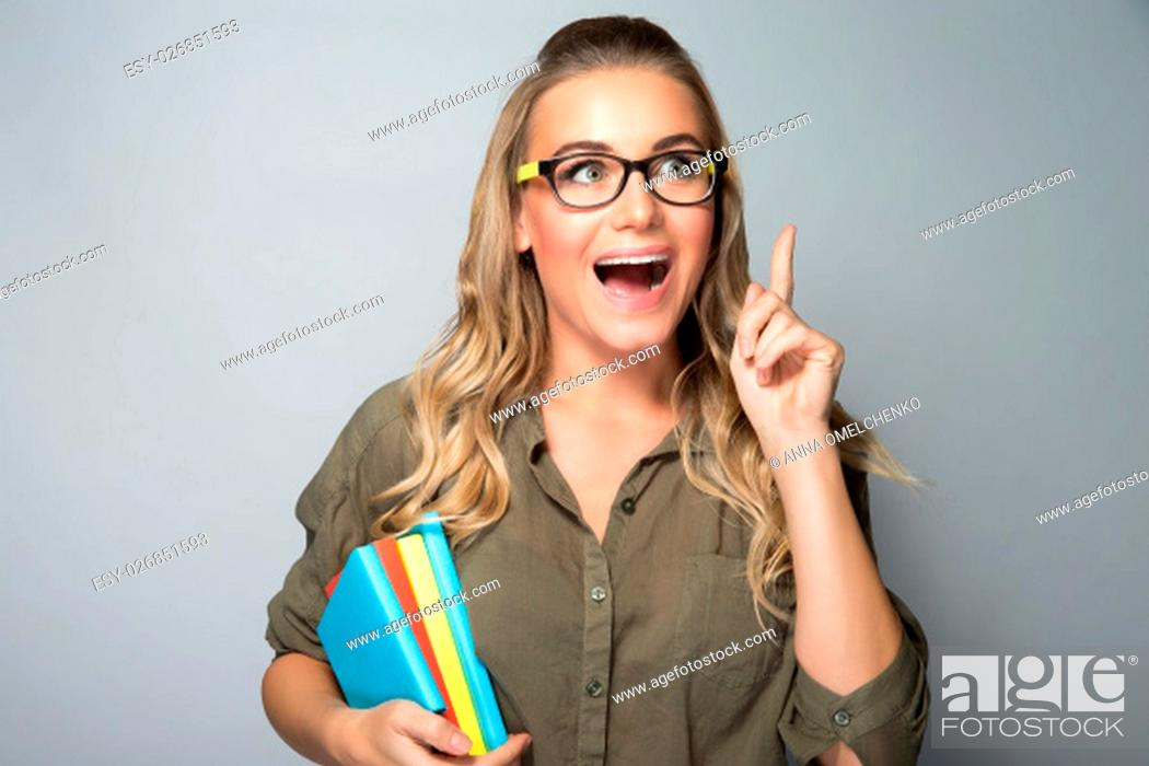 Stock Photo: Portrait of a clever student girl, brilliant idea concept, excited woman standing with open mouth and finger up, shot over gray background.