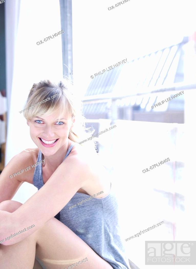 Stock Photo: Woman against window looking to camera.