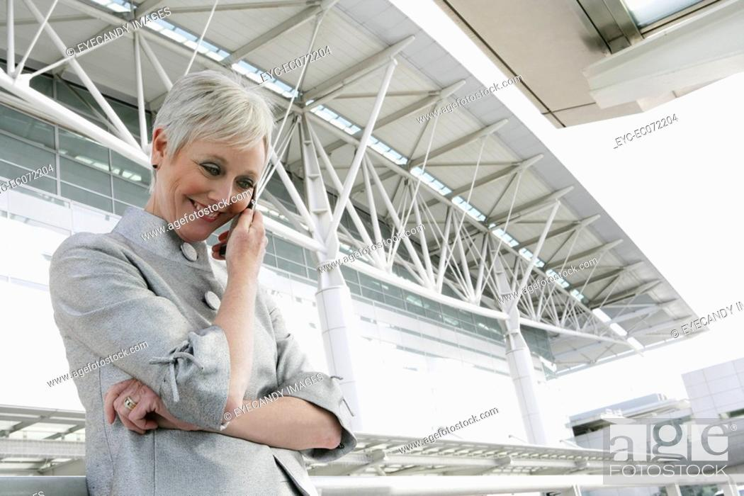 Stock Photo: Happy mature woman on the phone in front of airport.