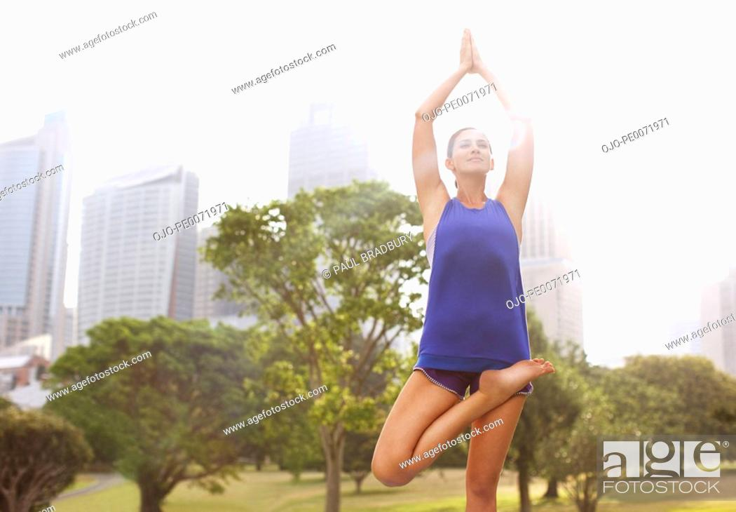 Stock Photo: Woman practicing yoga in park.