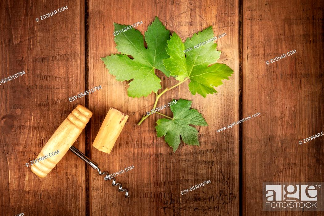 Stock Photo: A vine leaf with a vintage corkscrew and a cork, shot from above on an oak barrel.