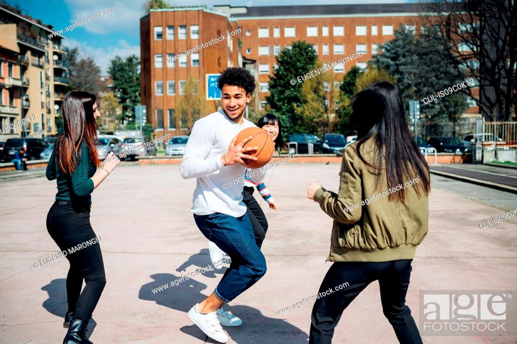Stock Photo: Young female and male adult friends playing basketball on city court.