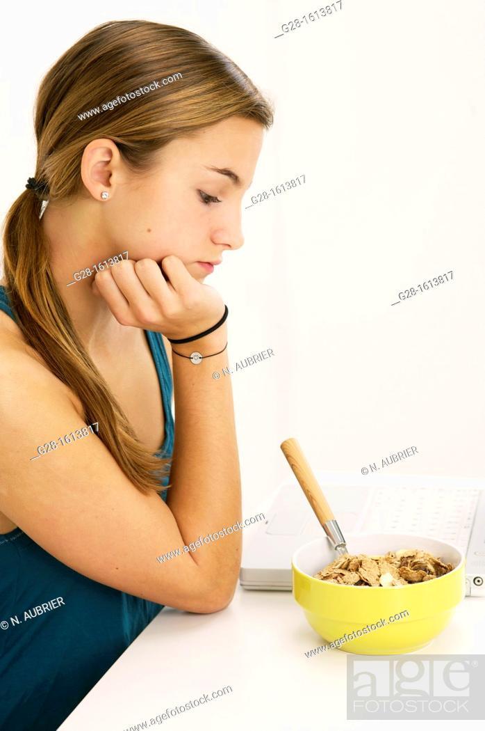 Stock Photo: Teenage girl refusing to eat her cereals suffering from anorexia.