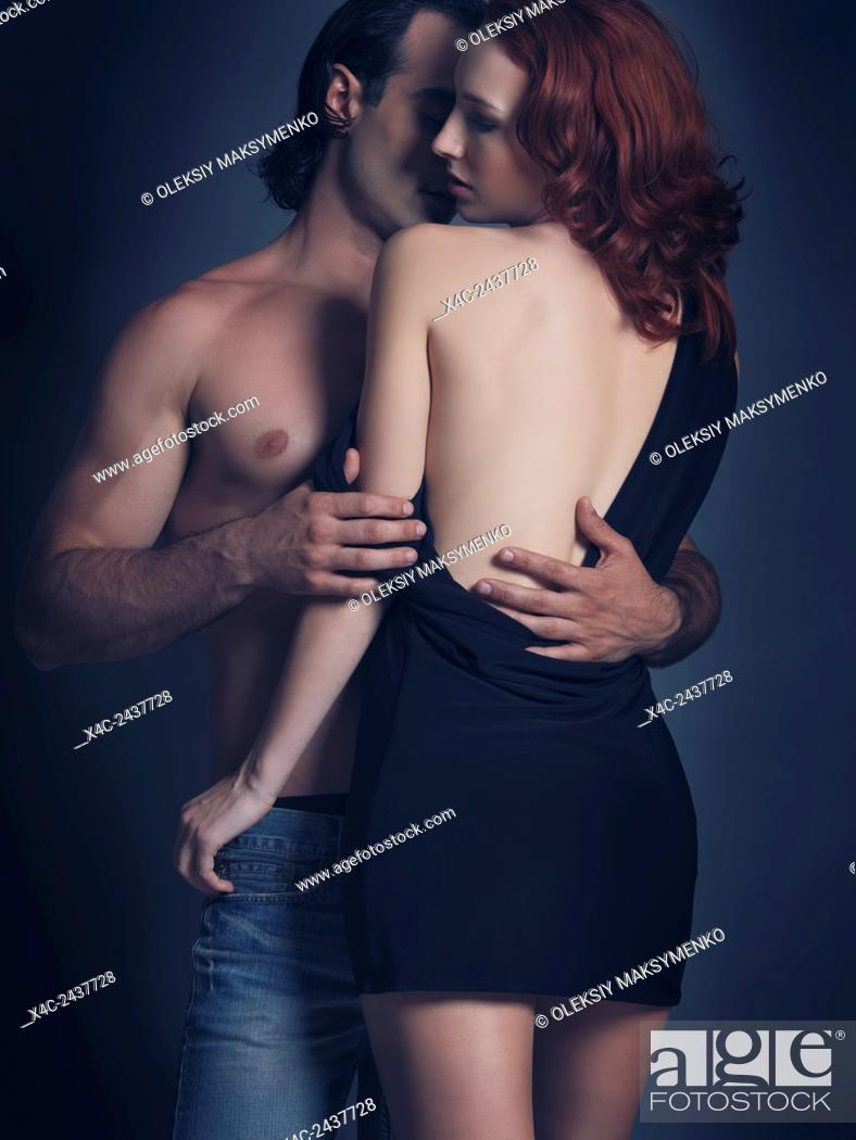 Stock Photo: Artistic soft sensual portrait of a young sexy couple. Man with bare torso embracing a woman in dress with open low back.